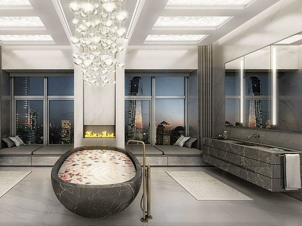 Kamine aus Stein und gläsernee Kronleuchter in schickem Wohnzimmer