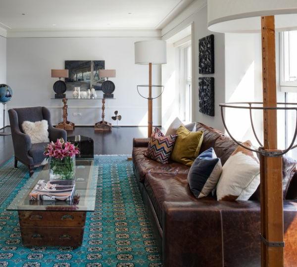 Dekokissen, braunes Sofa und schöner Teppich im Wohnzimmer
