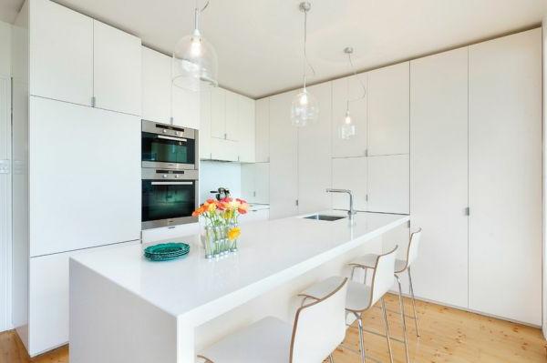 Drei Stühle und gläserne Kronleuchter in einer weißen Küche