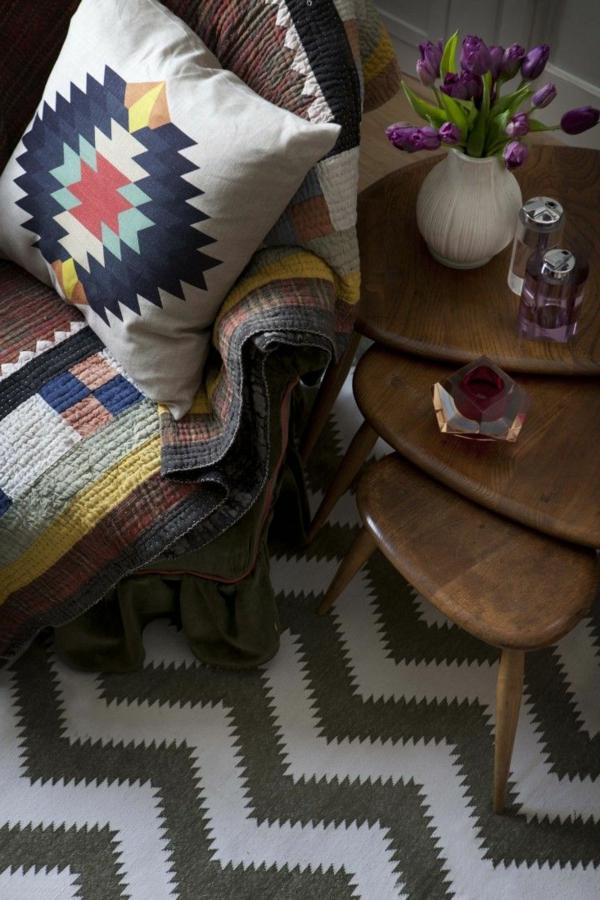 Wohnzimmer mit einem bunten Sessel und schönem hölzernen Nest Tisch