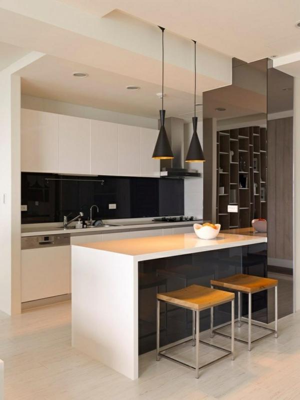 Weiße Kochinsel und schwarze Kronleuchter in einer modernen Küche