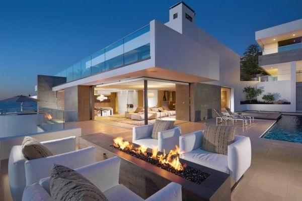 Terrasse aus Glass und luxus Feuerstelle im weißen Haus mit Blick aufs Meer