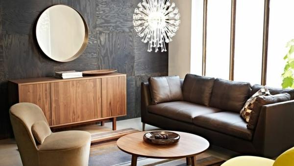 Rundes Spiegel, braunes Sofa und große Fenster im Wohnzimmer
