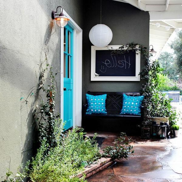 Schwarze Wandtafel und blaue Dekokissen im Eingang des Hauses
