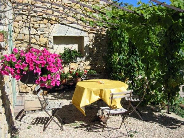 mediterrane terrasse mit einer wand aus stein un rosigen grellen blumen