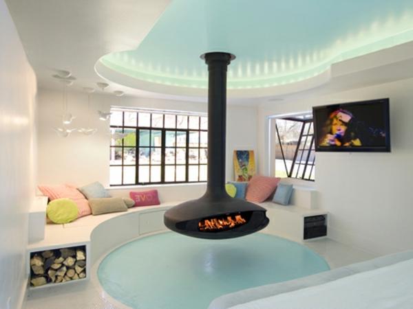 baddesign mit einer feuerstelle, bunten dekokissen, tv und große fenster