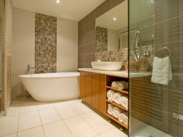 badezimmer mit einer großen weißen badewanne, einen waschtisch aus holz mit weißen tüchern