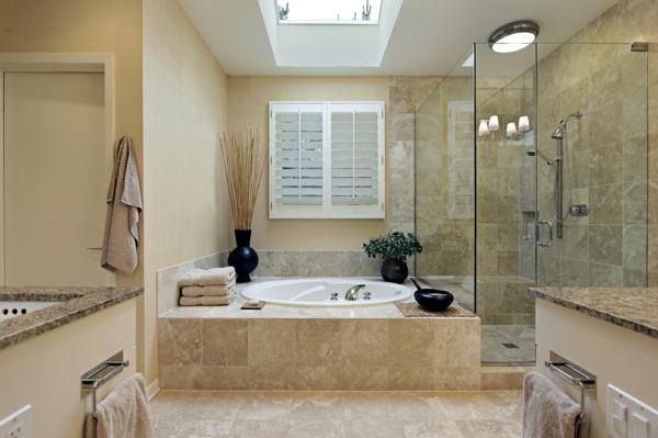 badezimmer gestaltung mit einer badewanne aus marmor und großer duschkabine aus glas
