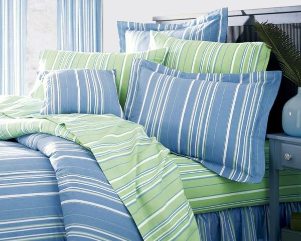 schlafzimmer mit bettwäschen und kissen in blauen weißen und grünen linien