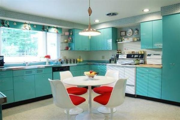 blaue küche mit rotem akzent-dekokissen auf den stühlen
