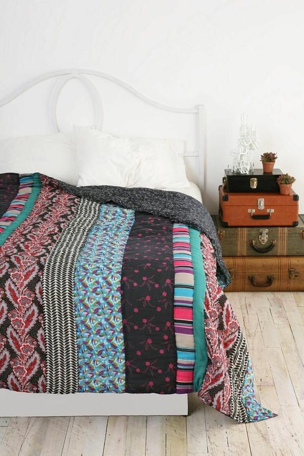 schlafzimmer mit einem bett mit bunten bettbezügen und weißen kissen