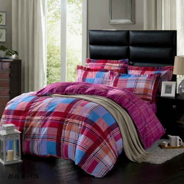 schlaffzimmer mit einem bett mit zyklamenfarbigen bettbezügen und kissen