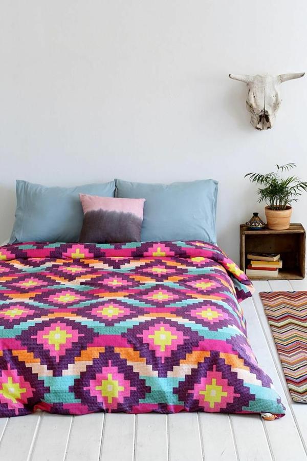 schlafzimmer mit einem bett mit bunten grellen bettbezügen