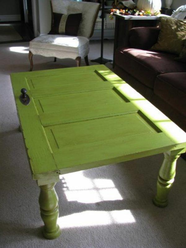 wohnzimmer mit einem selbsgemachen caochtisch design von einer grünen tür