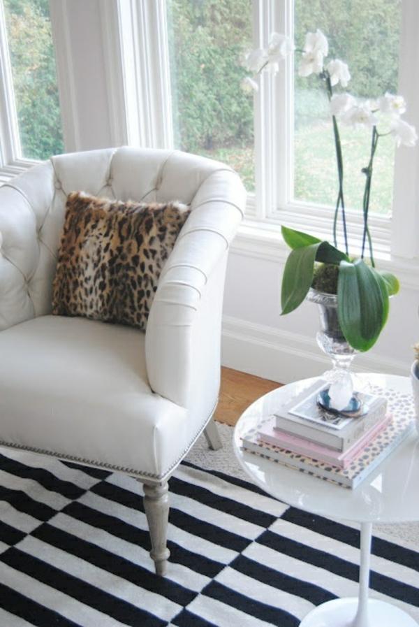 wohnzimmer mit einem weißen sessel, weiße blumen, dekokissen leopard und einem fenster