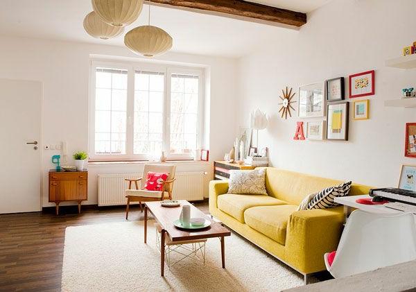 wohnzimmer modern miit einem gelben sofa , kugelförmigen kronleuchtern und dekoartikeln einrichten