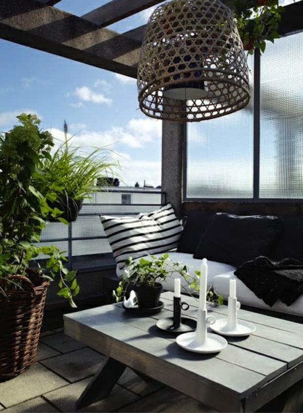 balkongestaltung mit interessantem kronleuchter, kerzen am tisch und dekokissen