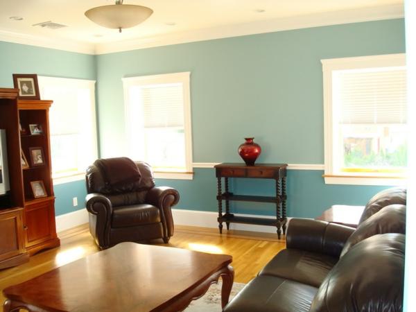 kleines wohnzimmer mit modernen möbeln und schöner wandgestaltung in blau