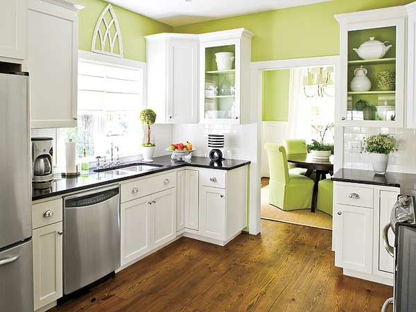 grüne wände weiße schränke und metallische elemente in der küche