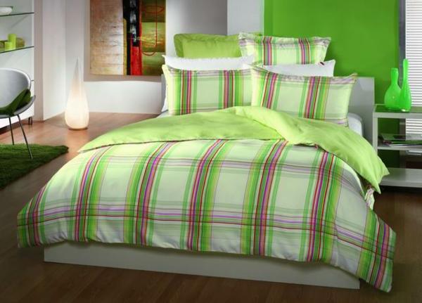 schlafzimmer mit einem bett mit bettwäschen und kissen mit geometrischen linien in grün