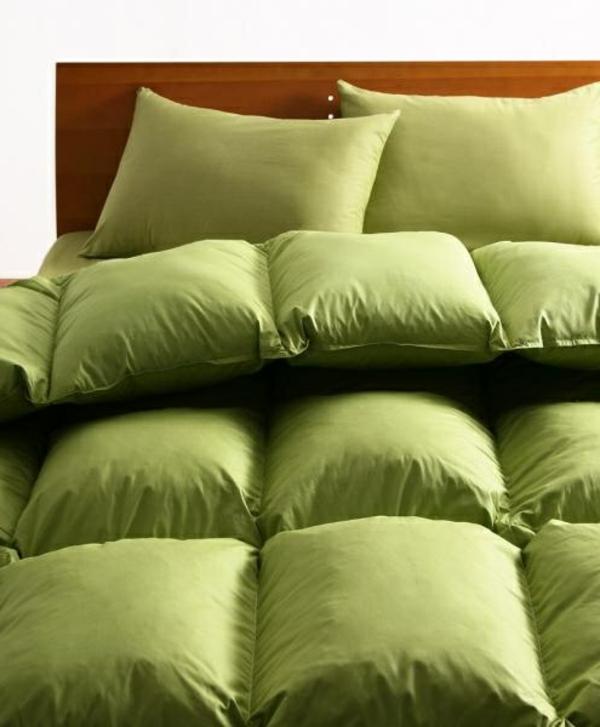 schlafzimmer mit grünen bettbezügen und kissen
