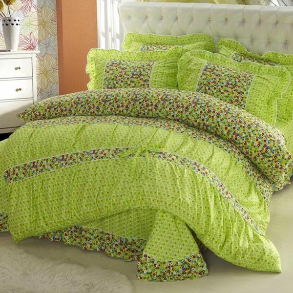 schlafzimmer mit einem bett mit bunten grünen bettbezügen und weißem kopfbrett
