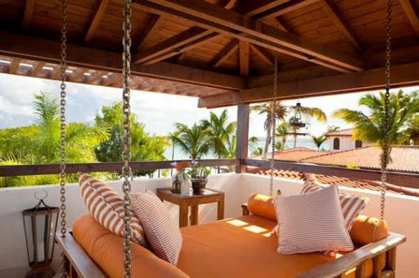 hängendes bett in orange auf einer modernen hölzernen terrasse mit schönem blick
