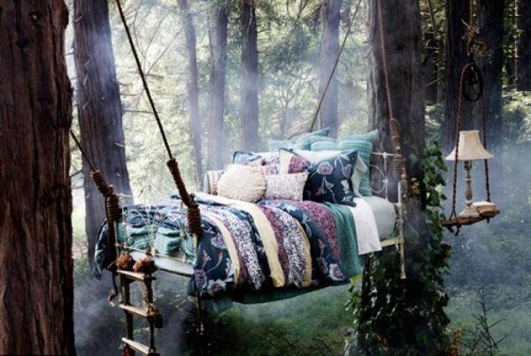 hängendes bett mit dekokissen - zwischen den bäumen im wald