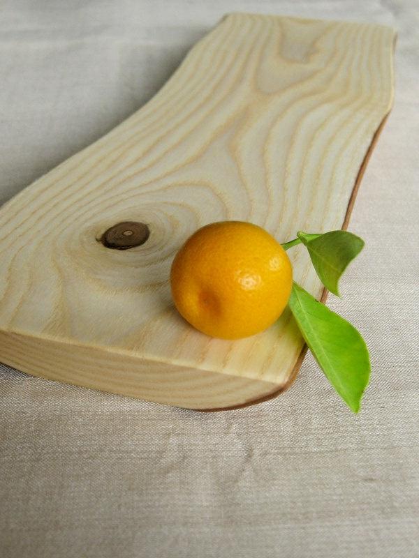 kleine mandarine auf einem holzbrett für die küche
