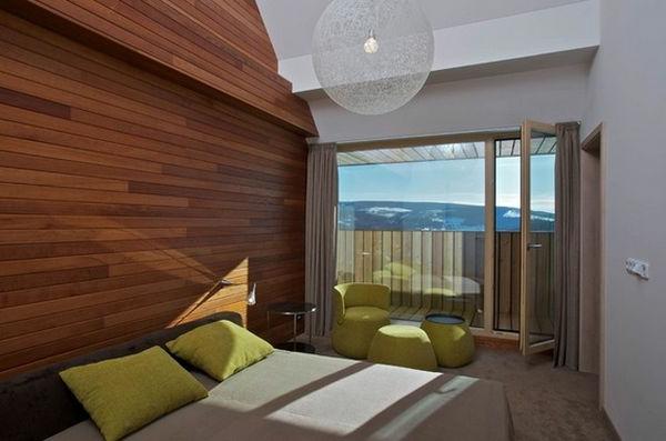 schlafzimmer mit holzwand und glaswand grüne kissen und runder kronleuchter