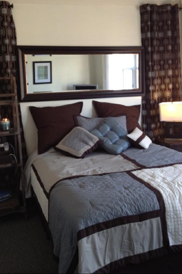 Originelles Modell vom Bett mit einem luxus Spiegel und gardinen in dunklen Farben