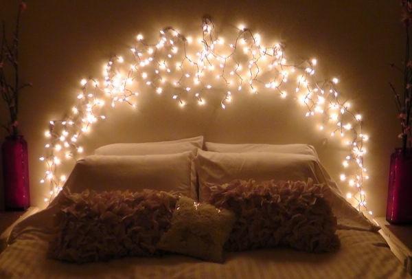 Schönes Design vom Bett mit warmer Beleuchtung und weichen Kissen