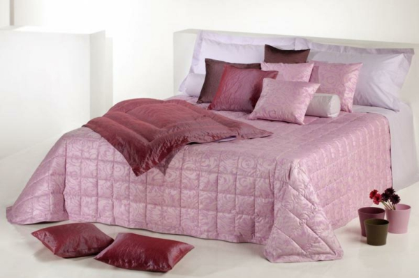 schlafzimmer mit einem bett mit rosigen und lila bettbezügen und kissen