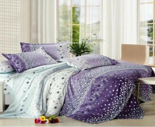 schlafzimmer mit einem bett mit bettbezügen in lila nuancen