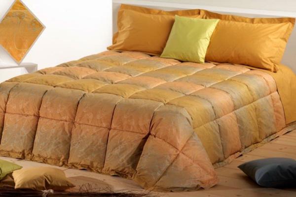 schlafzimmer mit einem bett mit bettbezügen und kissen in orange