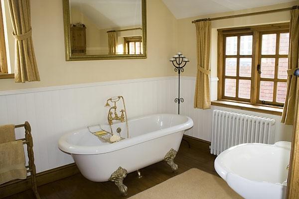 luxus badewanne und goldfarbige vorhänge im badezimmer