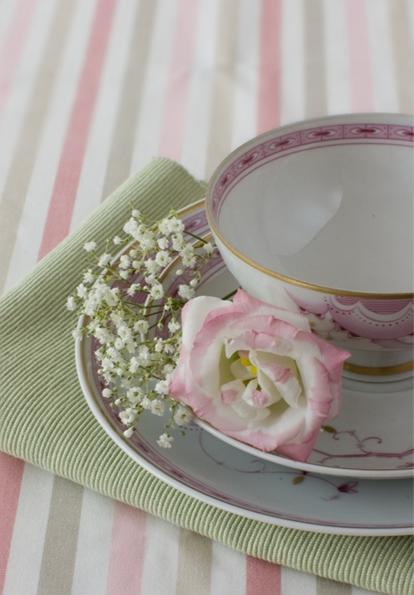tisch mit einer schönen rosigen decke und porzellanteller mit weißen blumen dekorieren