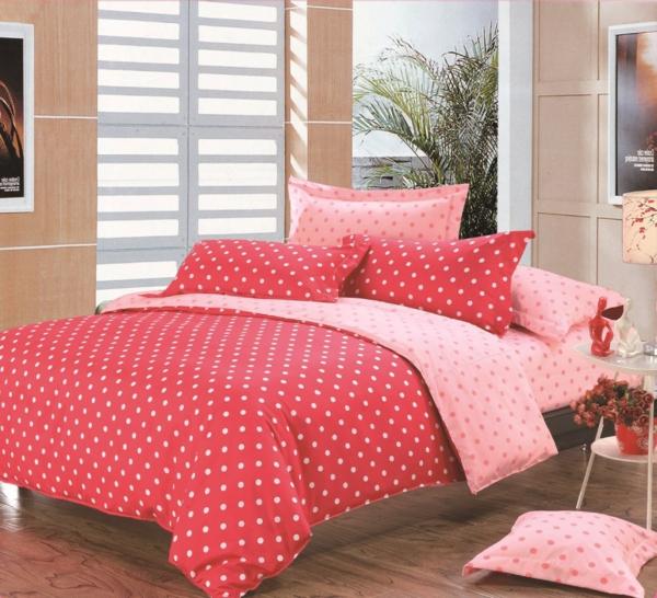 schlafzimmer mit einem bett mit bettbezügen und kissen - punkte