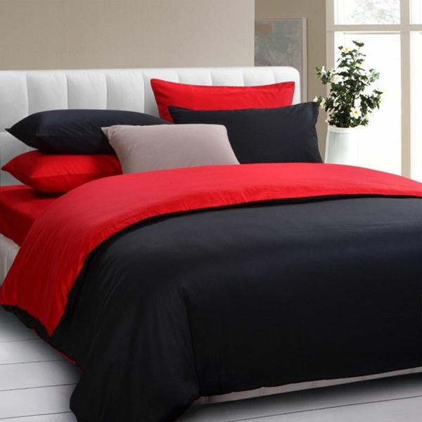 schlafzimmer mit einem bett mit bettbezügen in rot und schwarz