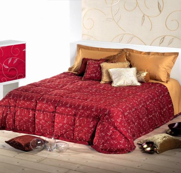 schlafzimmer mit einem bett mit bettbezügen und kissen in roten und goldenen farben