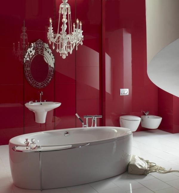 baddesign mit roten wänden und luxus kronleuchter und rundem spiegel