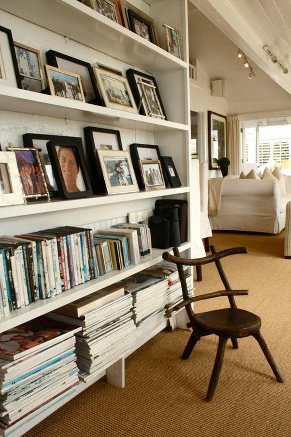 Schwarze und weiße Rahmen von Bildern auf Regalen im Hausflur