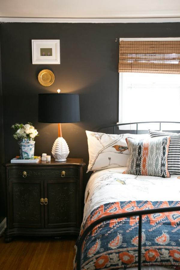 schlafzimmer mit schwarzer wandgestaltung - bett mit weißen und bunten bettwäschen und kissen