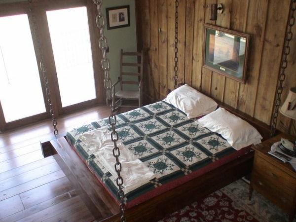 hängendes bett im schlafzimmer mit einer holzwand