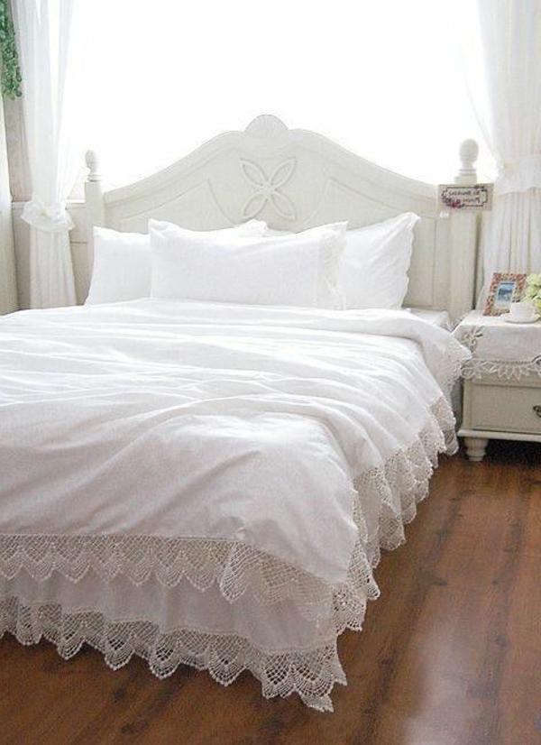 schlafzimmer mit einem bett mit bettbezügen und kissen in weiß