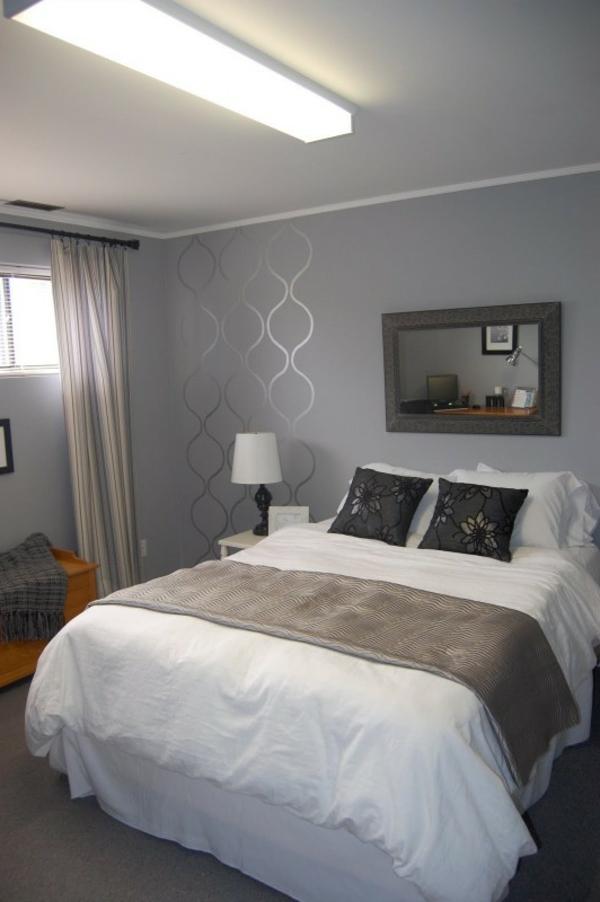 schlafzimmer mit einem großen bett,  graue wand und interessante bemalungen