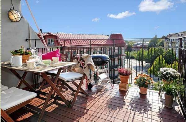terrasse mit schöner gestaltung - blumen und hölzernem tisch