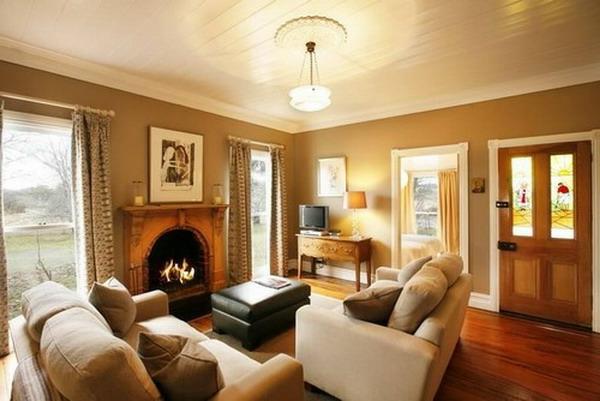 wohnzimmer ausstatten - weiches sofa kamin dekokissen große fenster ochra wandgestaltung