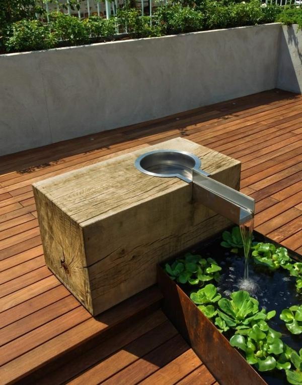 luxus brunnen auf einer terrasse mit grünen pflanzen und hölzernen brettern