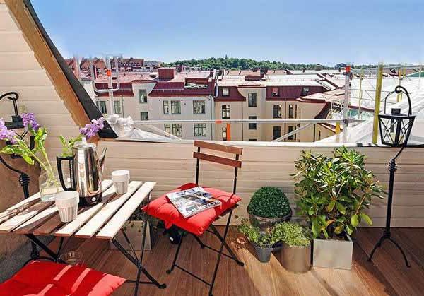 schöne balkongestaltung mit einem hölzernen tisch und rote akzenten